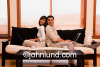 Hispanic couple at home on the sofa showing togetherness. They are back to back on the sofa and he has a laptop in his lap. They are smiling and happy.